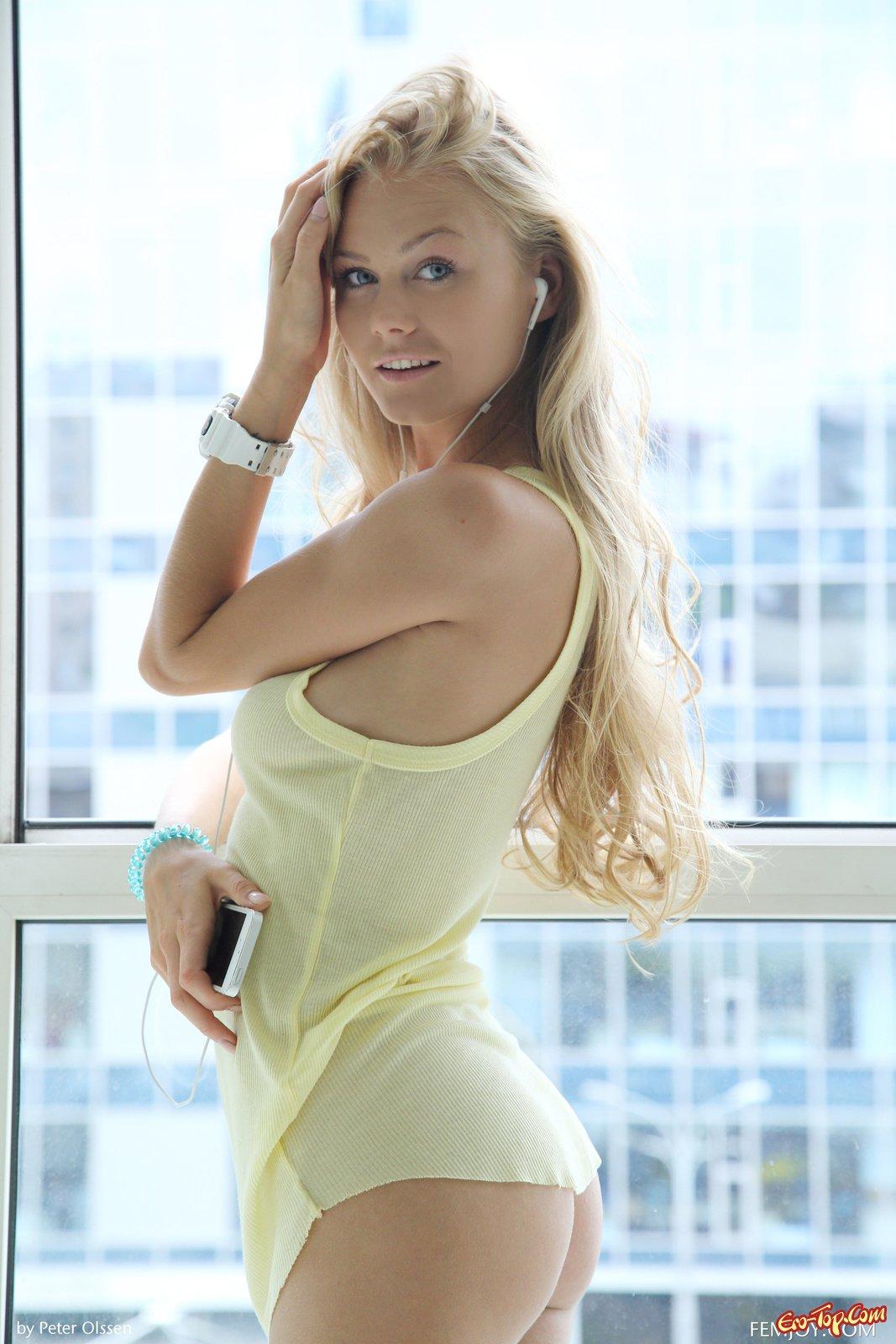 Обнаженная модель со свелыми волосами рядом с окном
