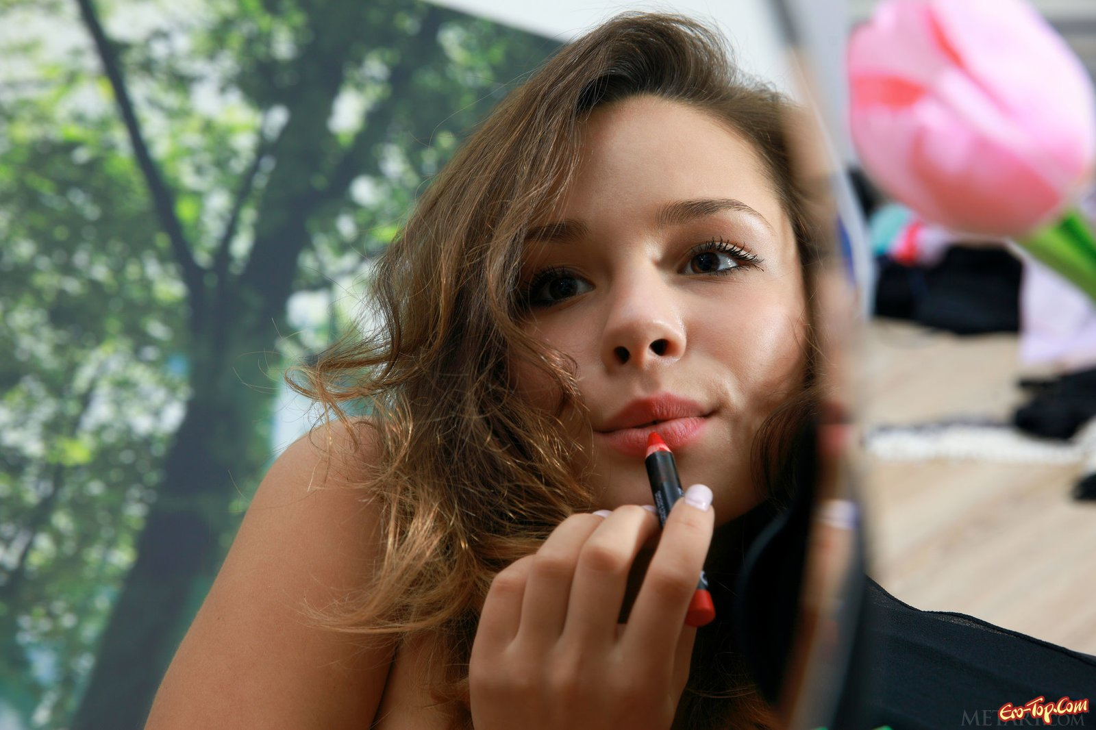 Голая девушка красится перед зеркалом