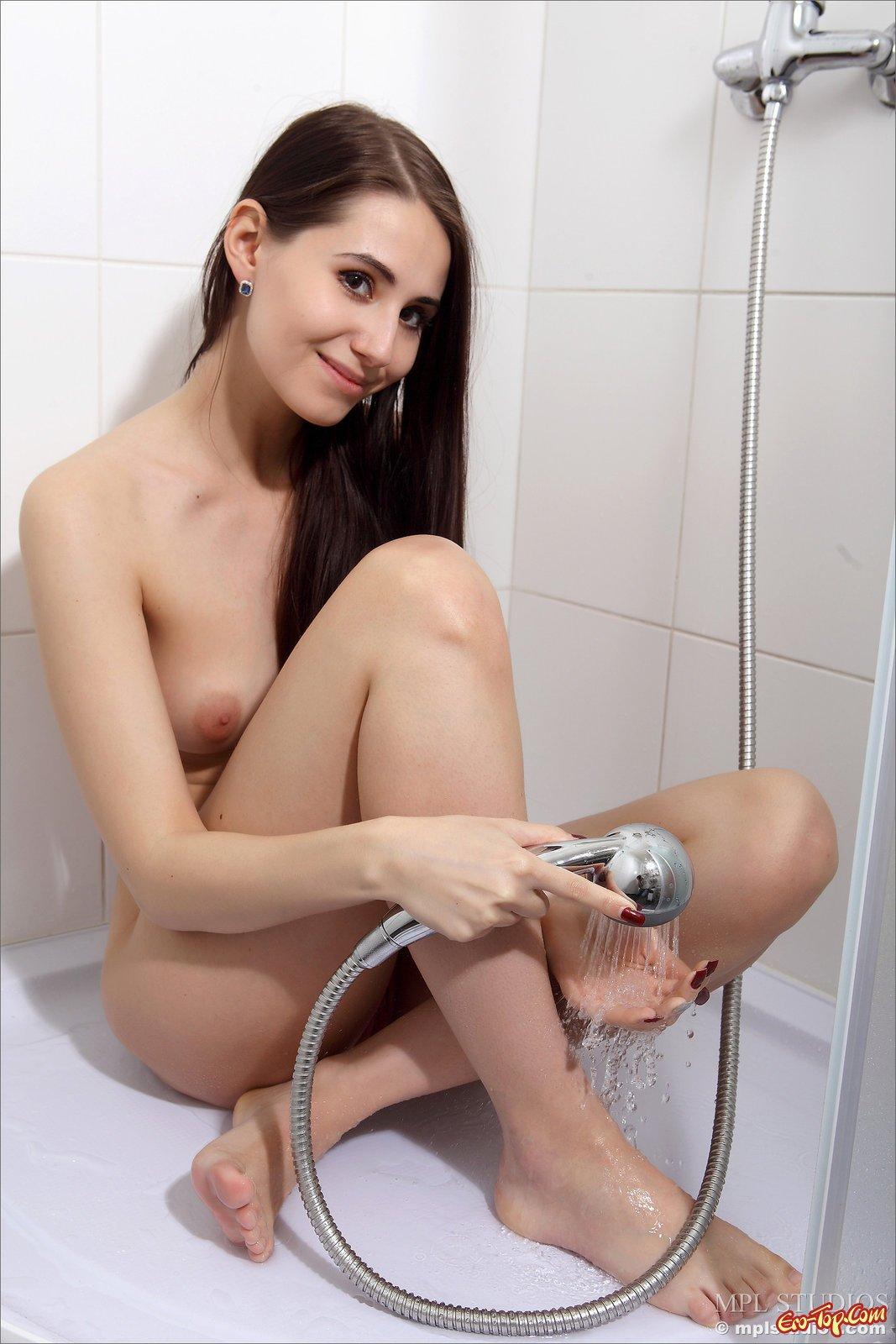 Титястая девка моется под струями воды