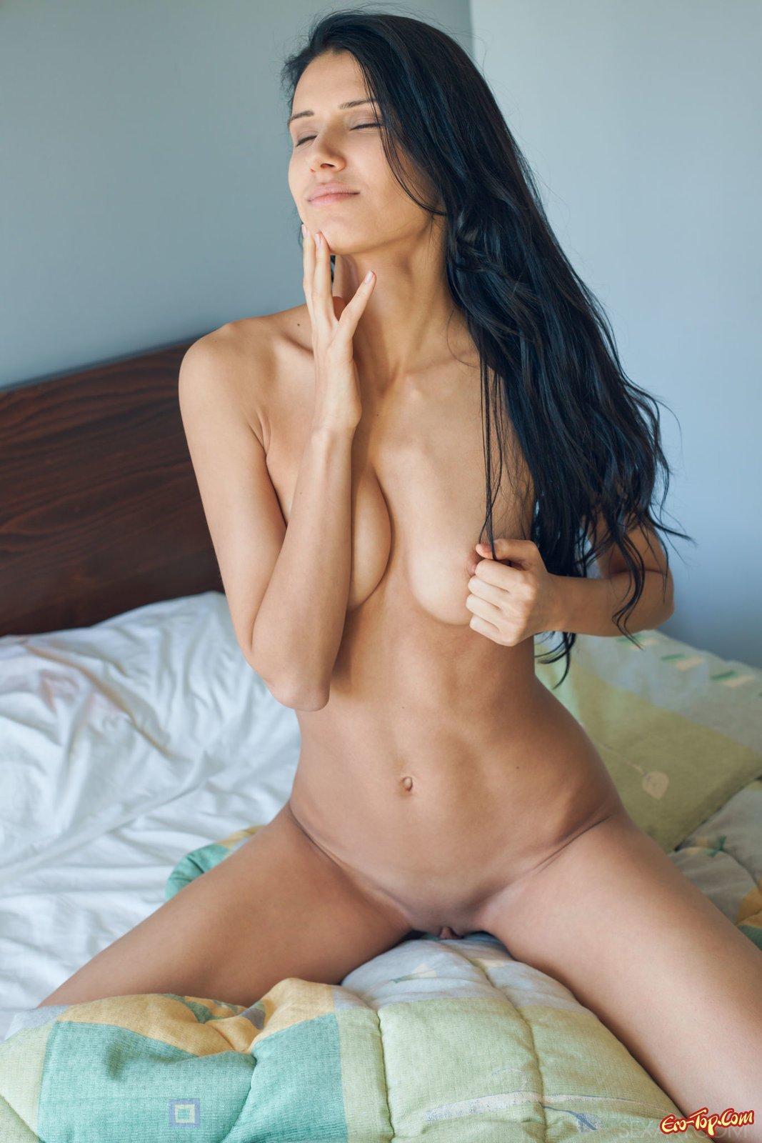 Хорошенькая брюнетка на кроватке