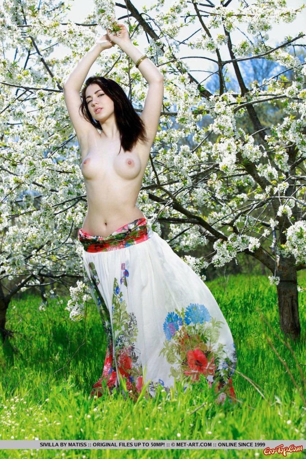 Красивая голая девка в цветущем парке