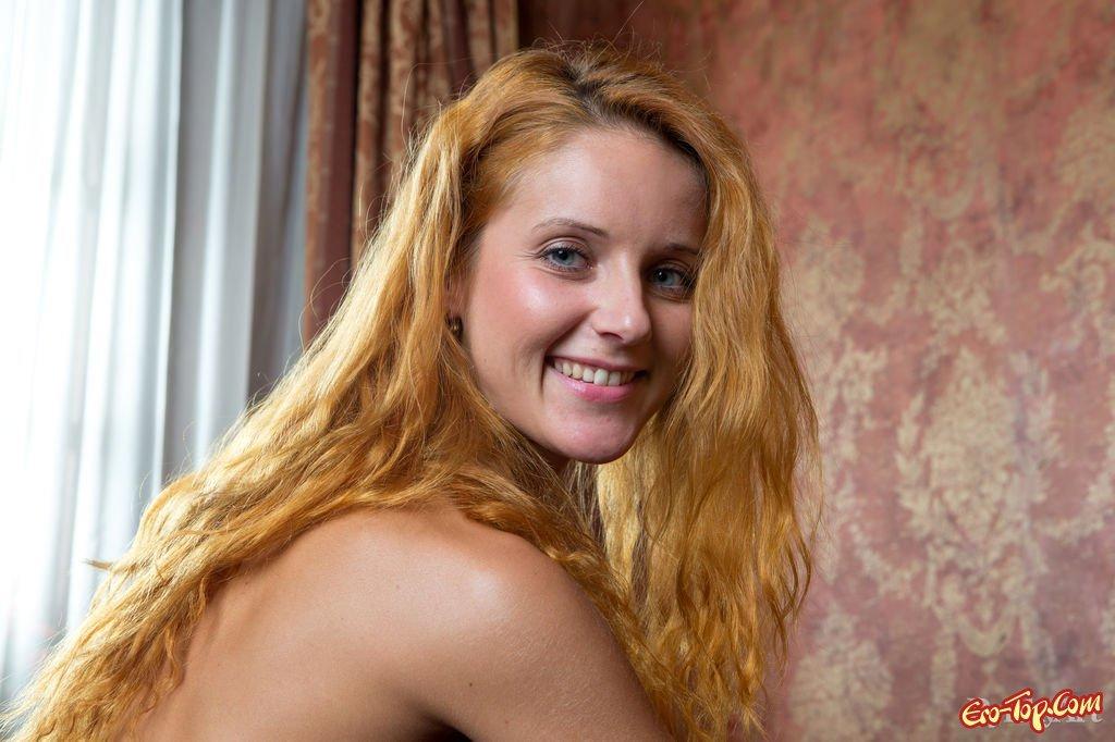 Рыжеволосая девушка позирует полностью голой