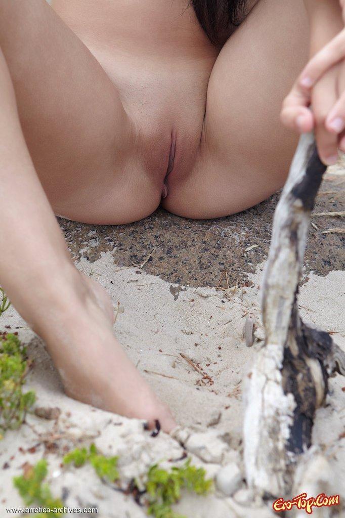 Раздетая тёлка сидит попкой у моря