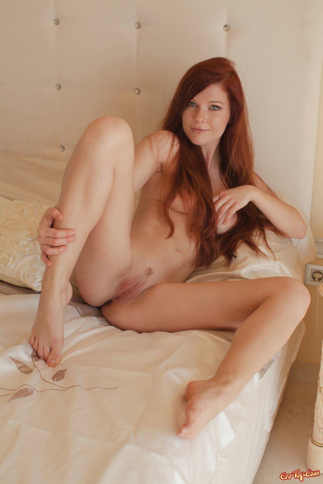 Рыжеволосая милашка раздевается и позирует в постели секс фото