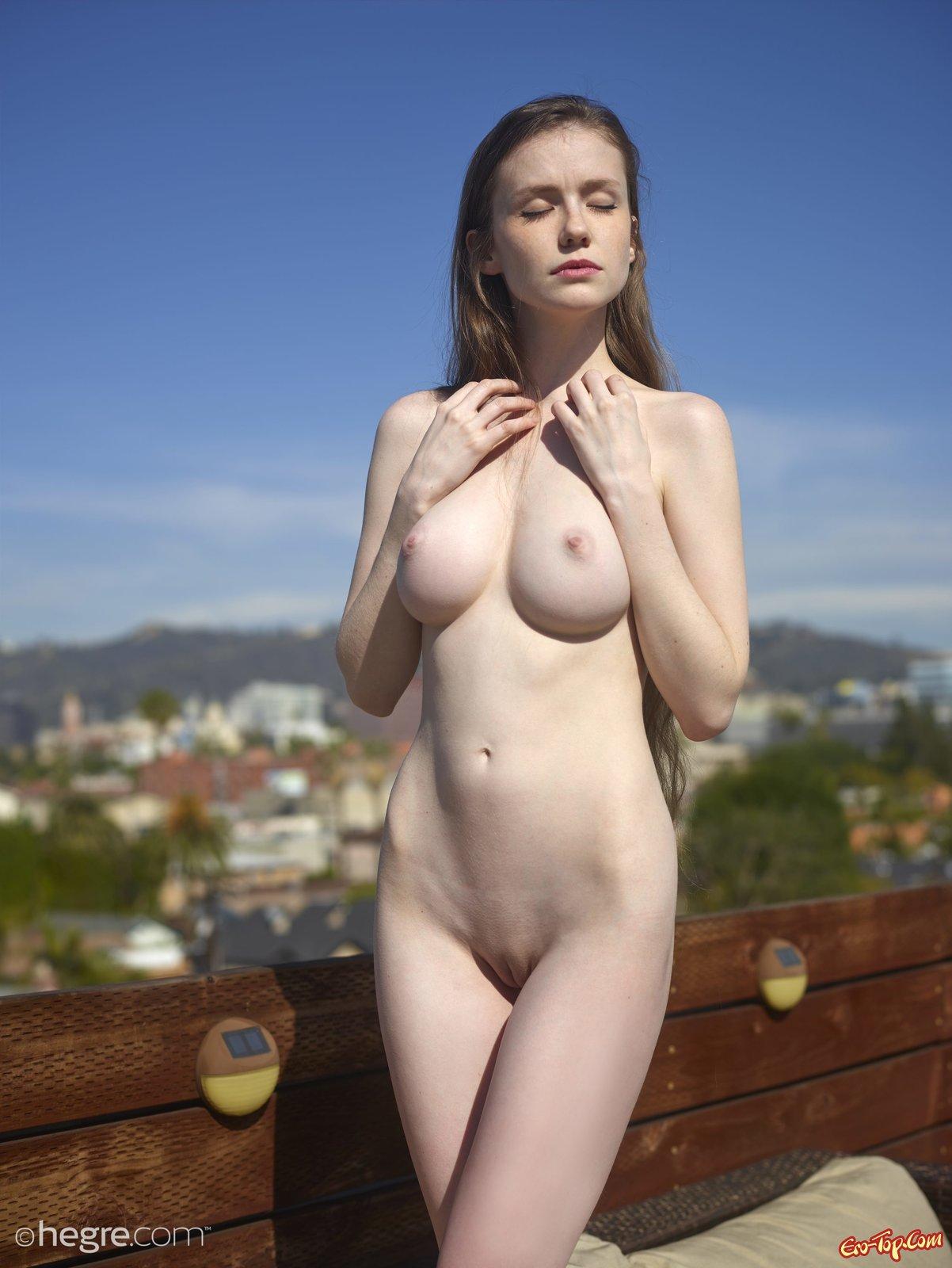 Стройная девушка позирует голой на крыше