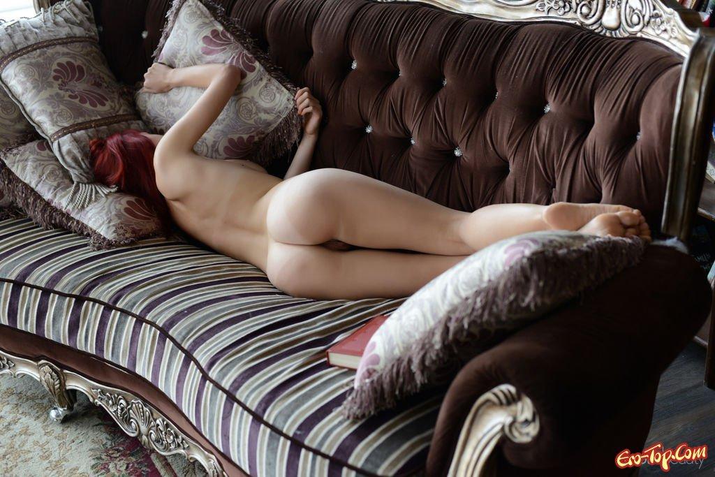 Рыжеволосая голенькая девушка читает