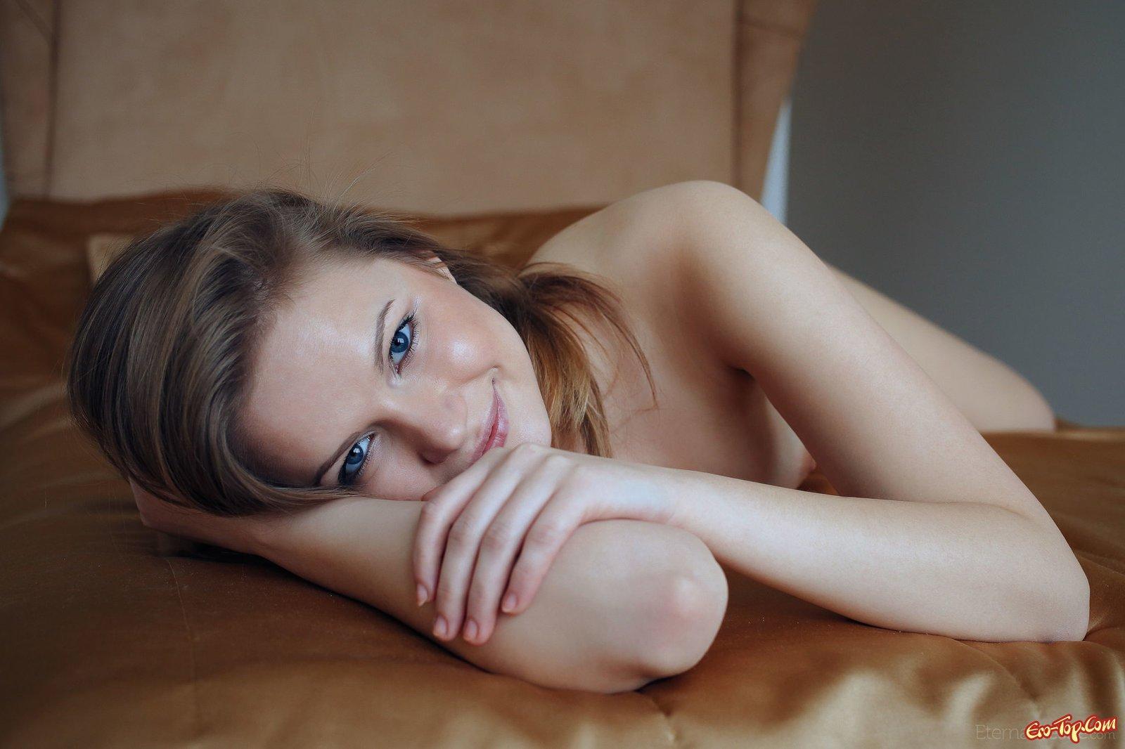 Симпатичная девушка голой позирует в постели