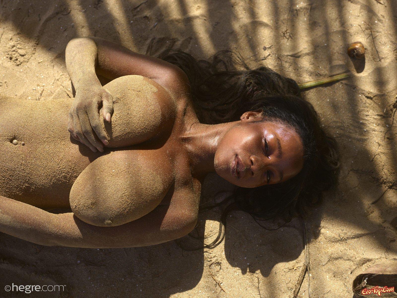 Негритянка с большой грудью валяется на берегу моря
