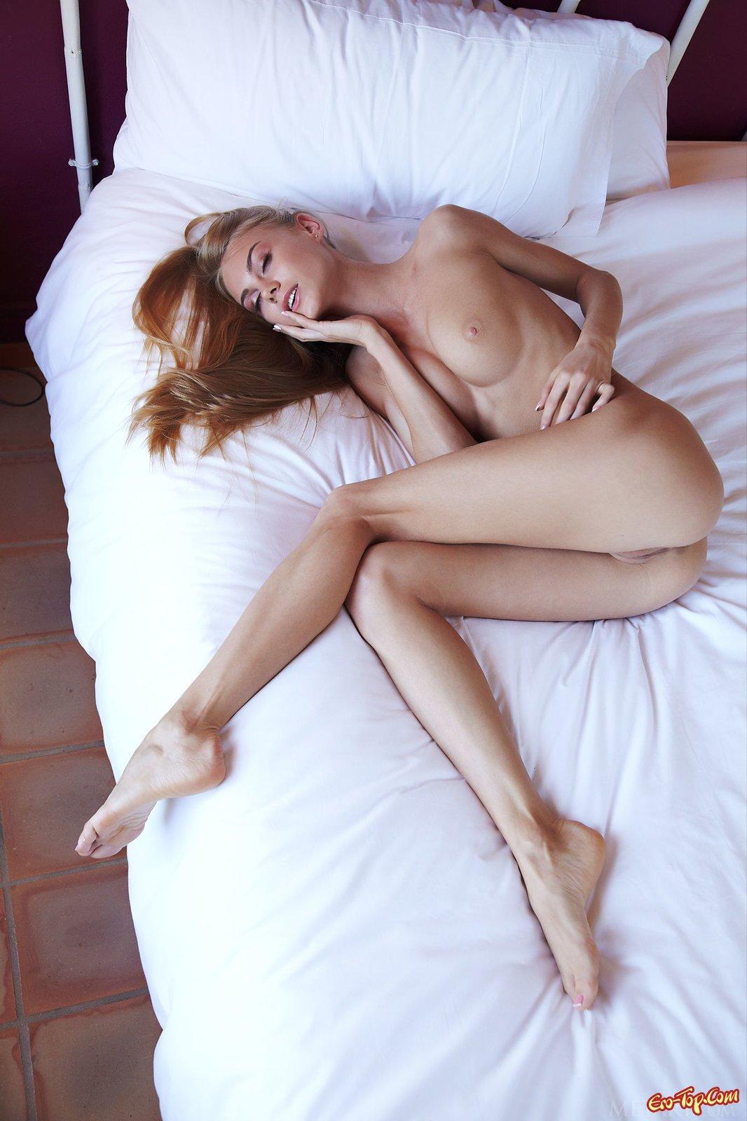 Привлекательная блондиночка обнажается в спальне