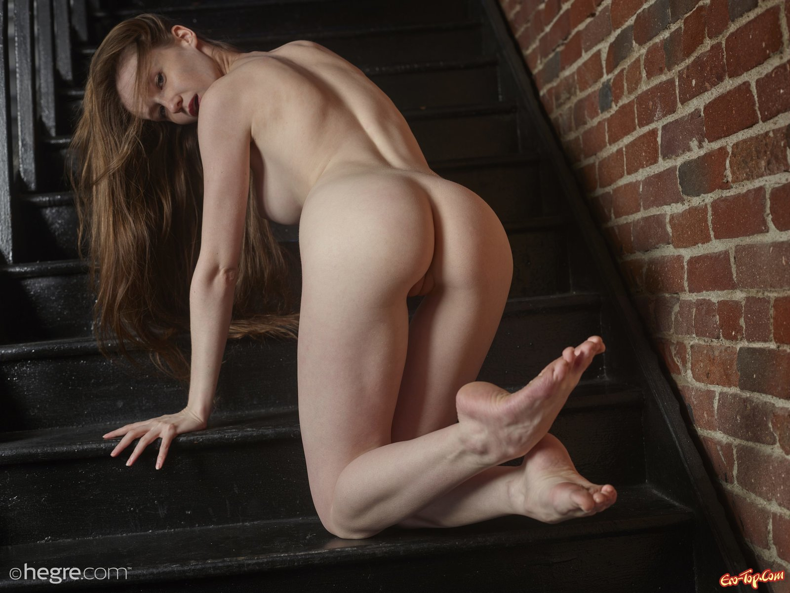 Голая красотка позирует на лестнице