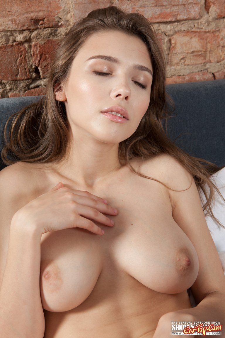 Нежная красотка сжимает грудь лежа в постели