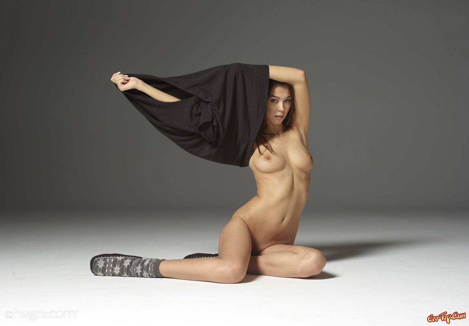 Девушка с длинными ногами позирует лежа на полу