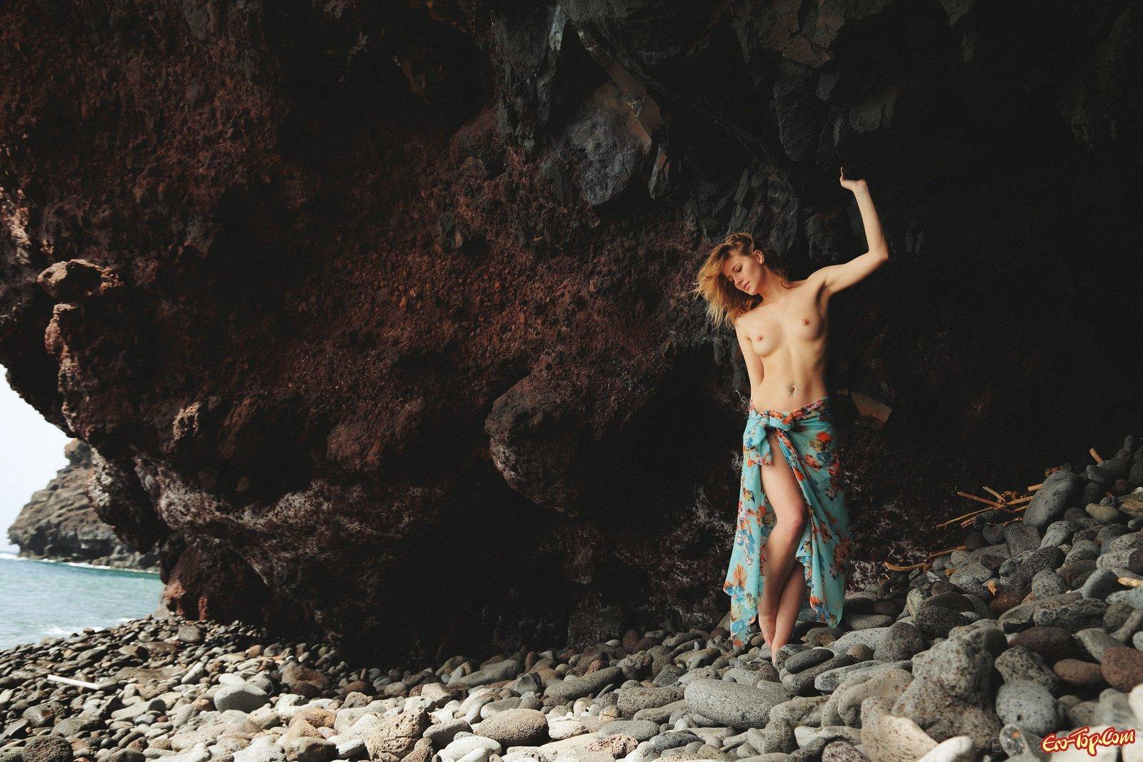 Блондинка ложиться голой на камни у моря