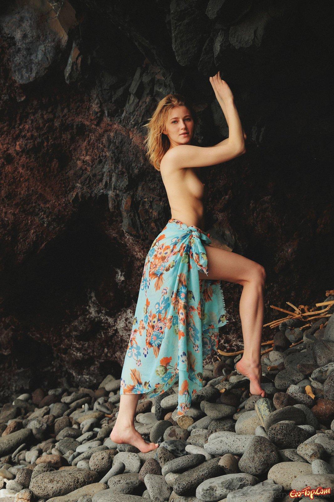 Блондинка ложиться голой на камни на берегу моря