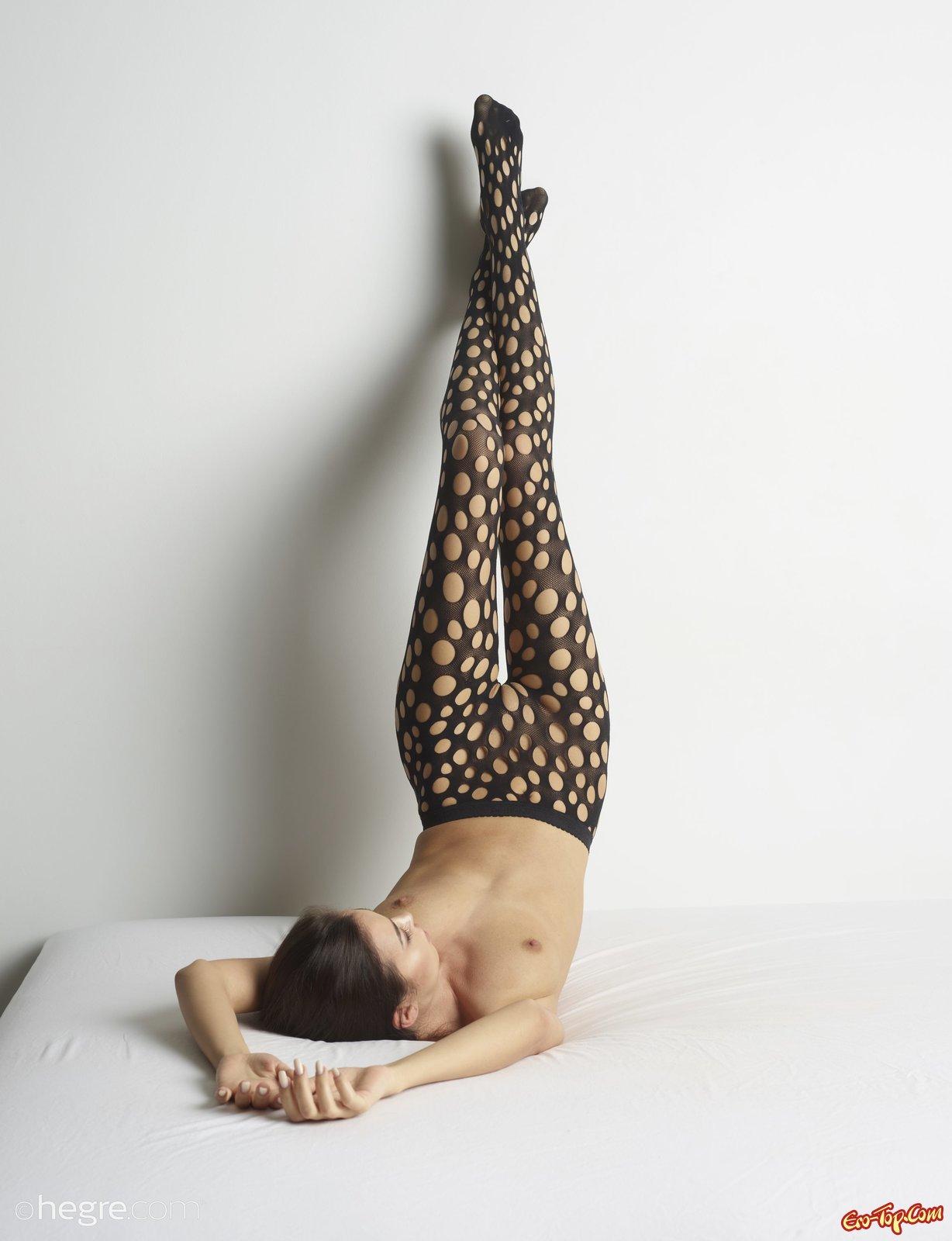 Стройная девушка в колготках позирует на кровати