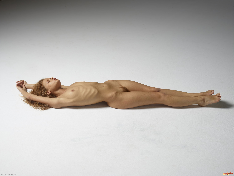 Нагая худосочная барышня фотографируется лежа на полу