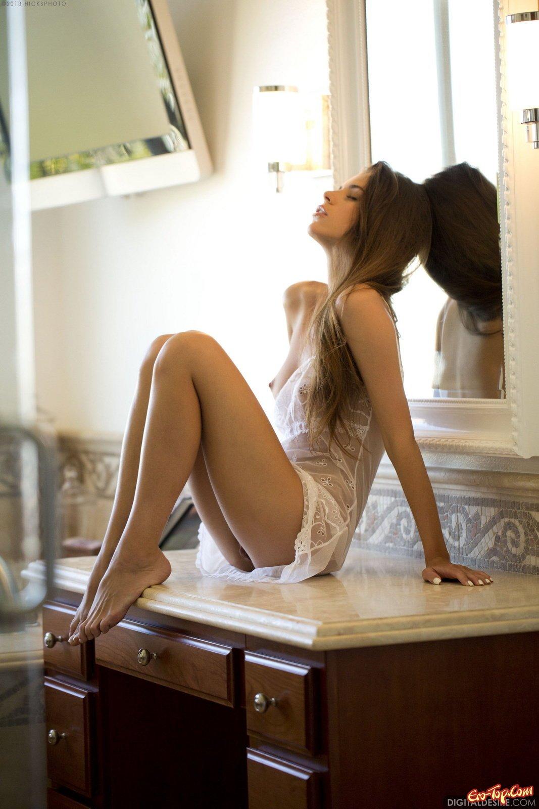 Красавица раздевается сидя у зеркала