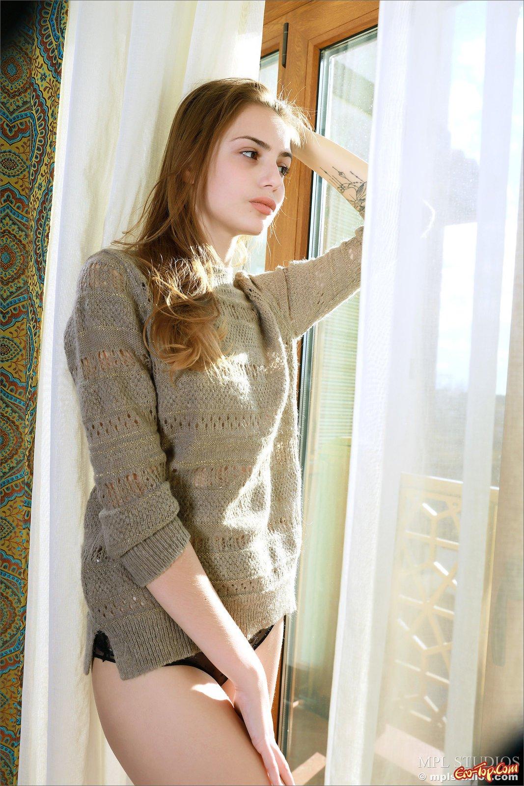 Худышка раздевается у себя в квартире возле окна