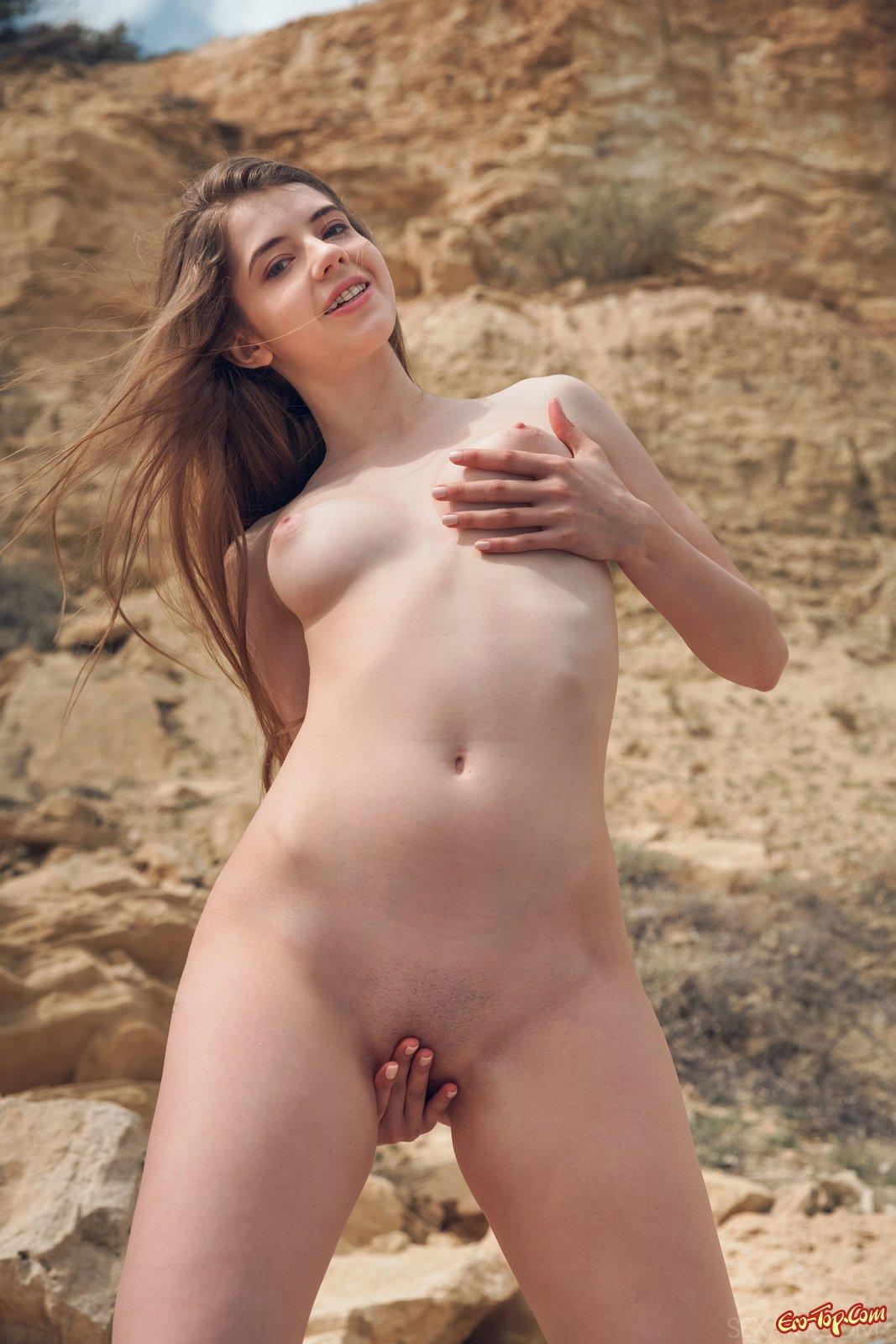 Голая модель эротично делает селфи на камнях на берегу моря секс фото