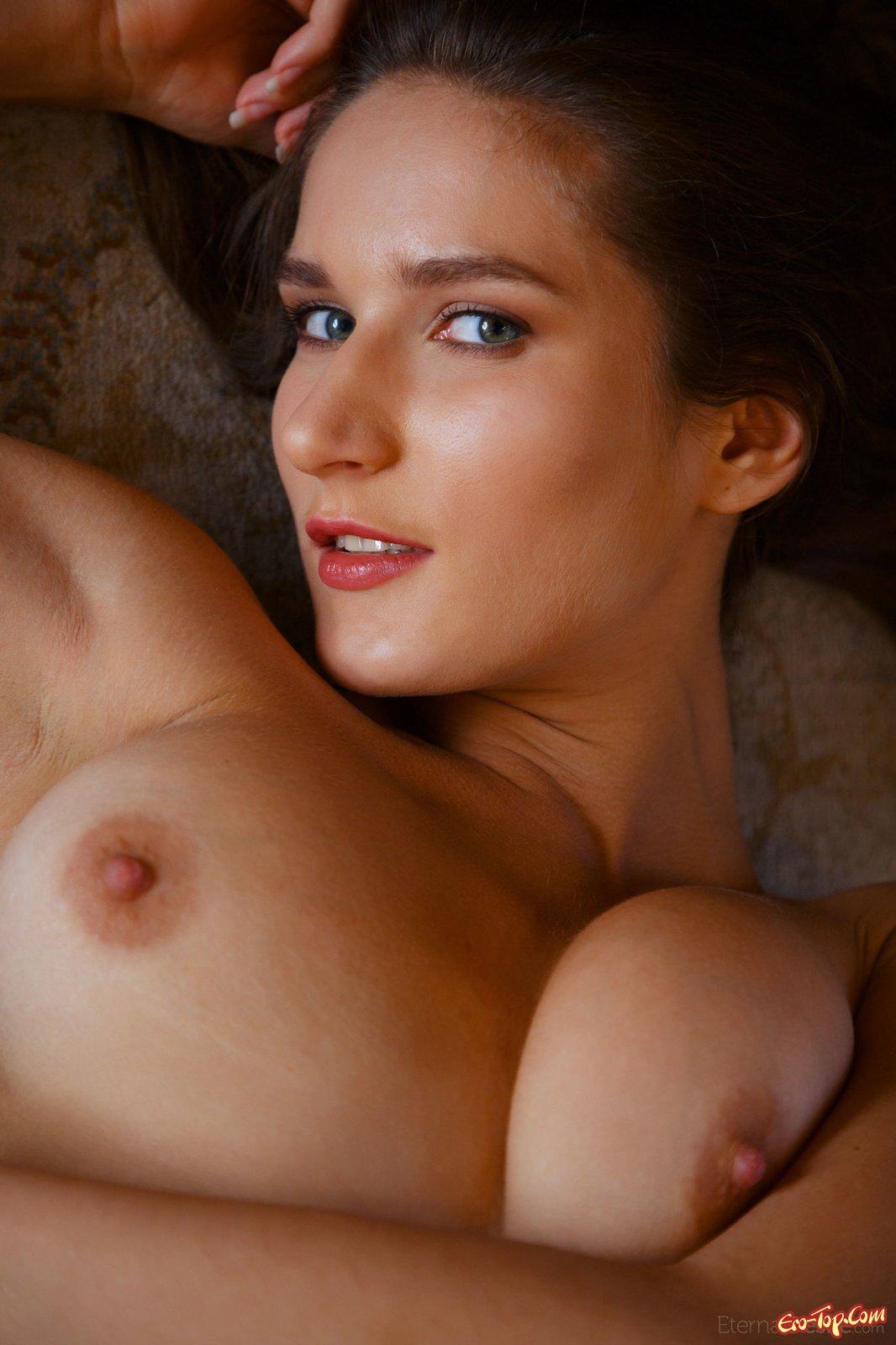 Красивая девушка расставляет ноги лежа на ковре