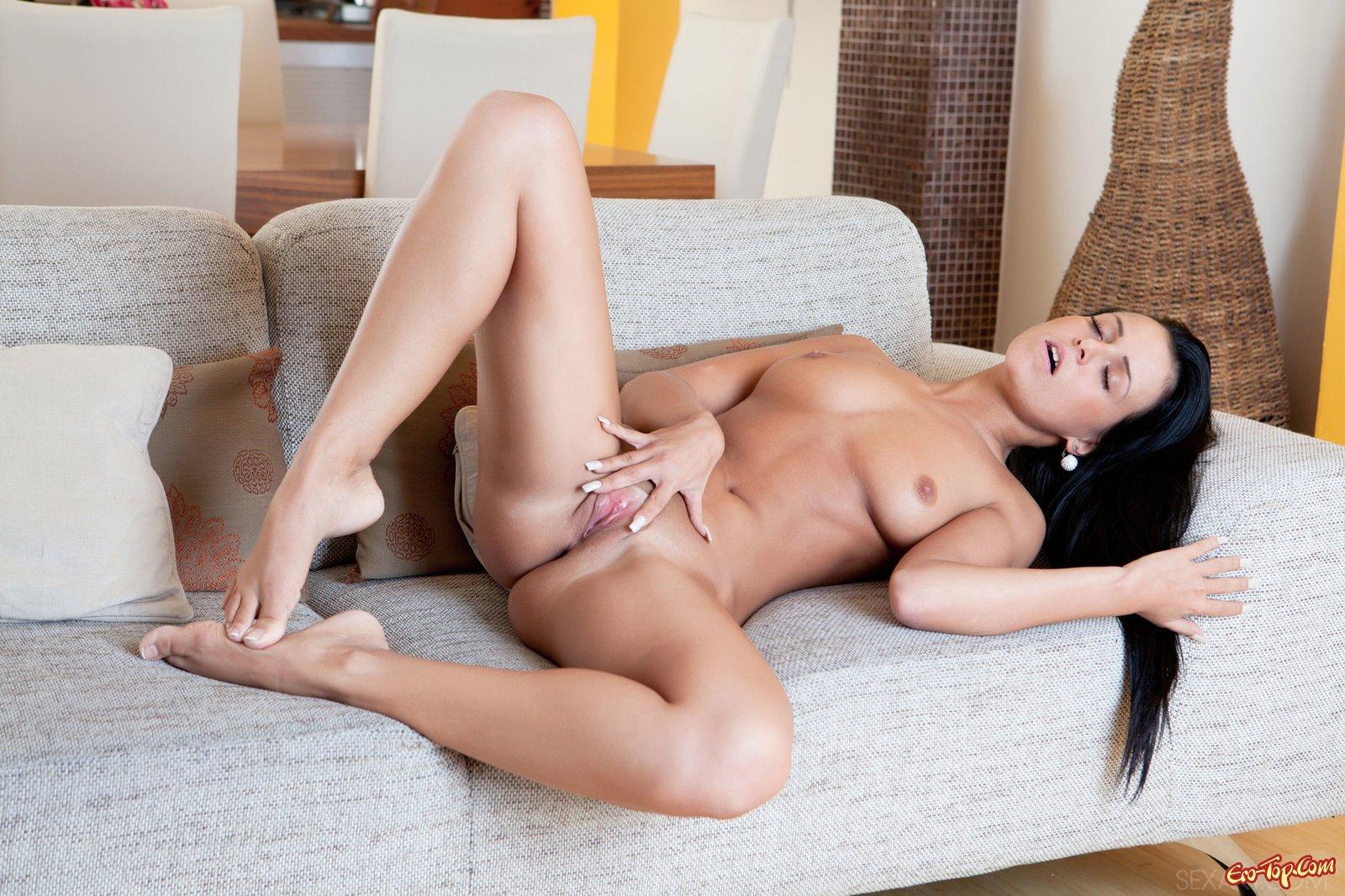 Брюнетка расставляет ноги дома на диване