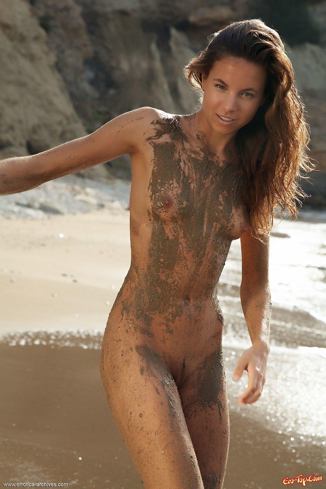 Загорелая девушка обмазалась грязью на море