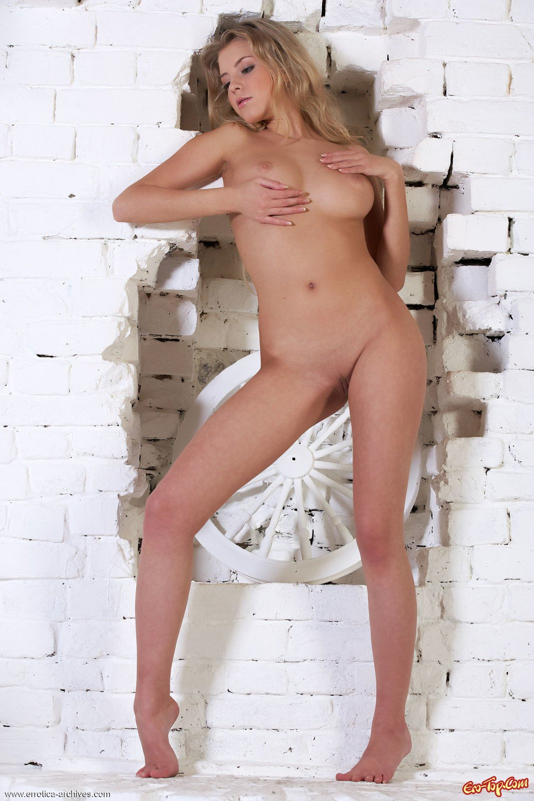 Голая блондинка оголяет вагину стоя у стены