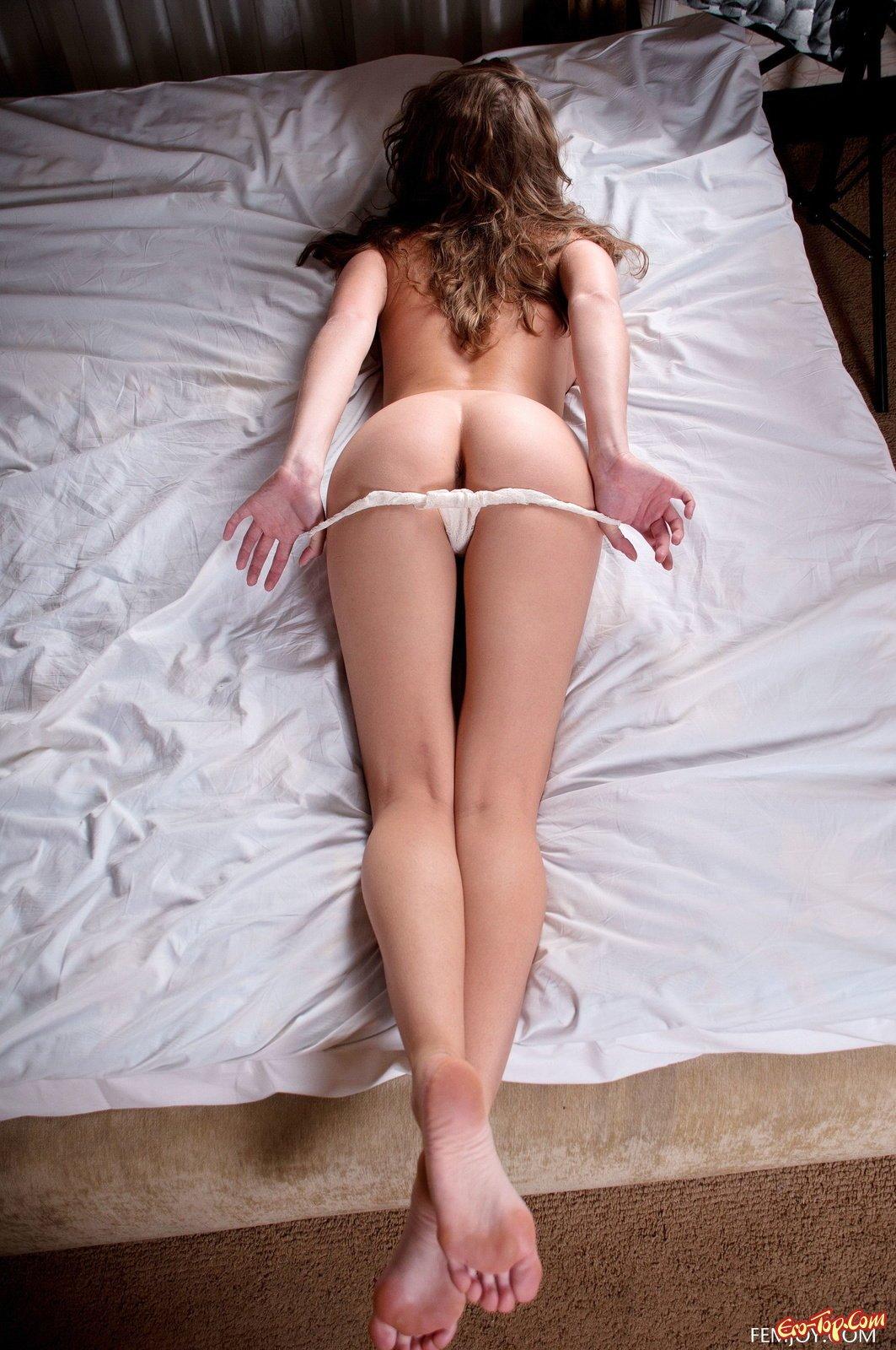 Красотка снимает трусики лежа на простыне