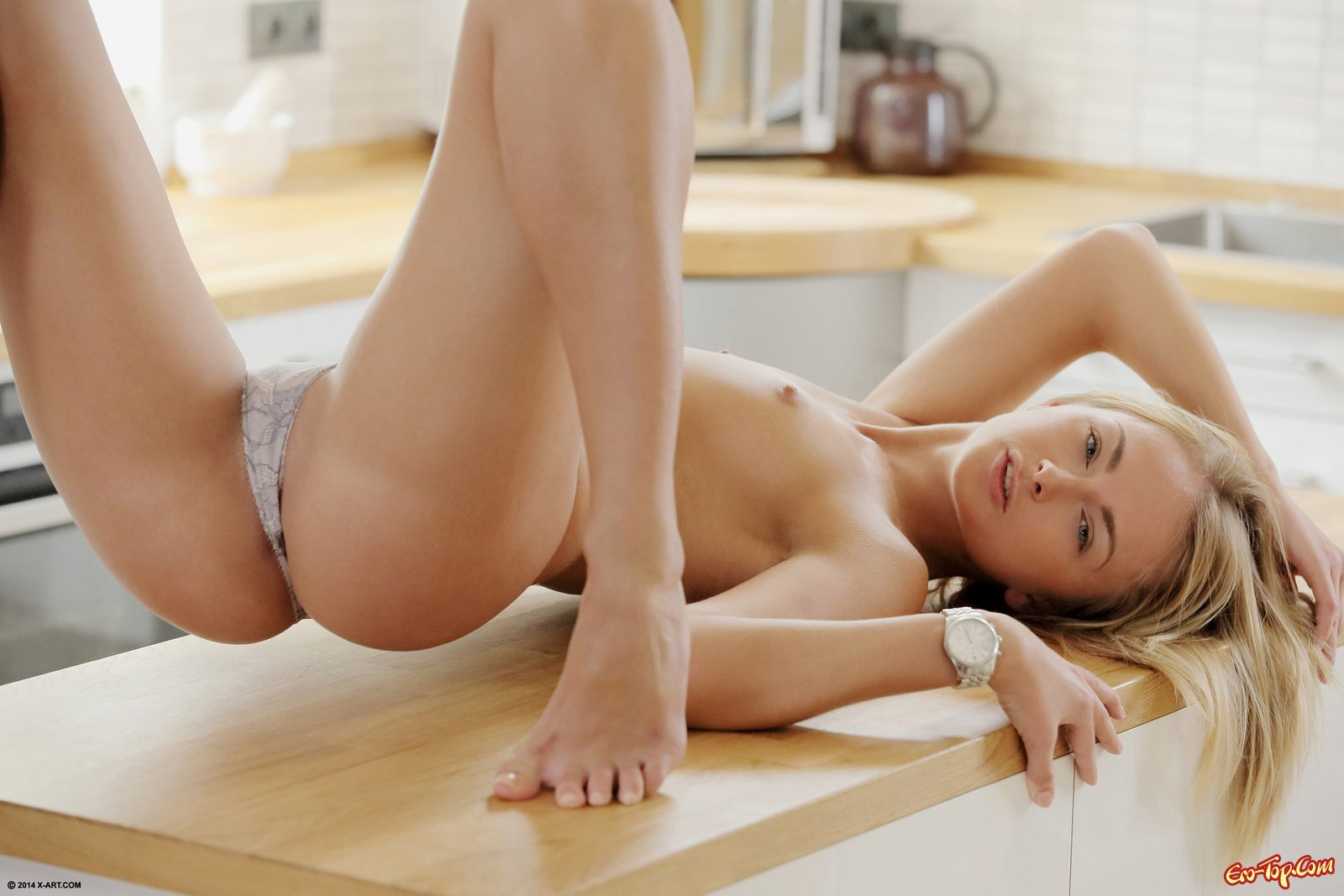 Блондинка показывает пилотку на кухонном столе