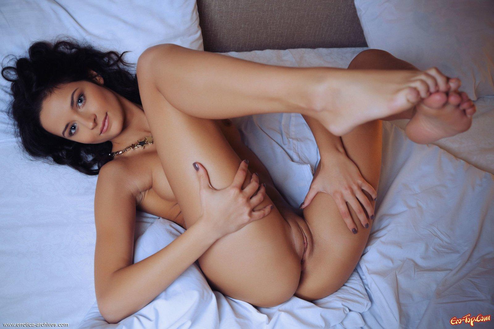 Смуглая красавица оголяет тело лежа в койке