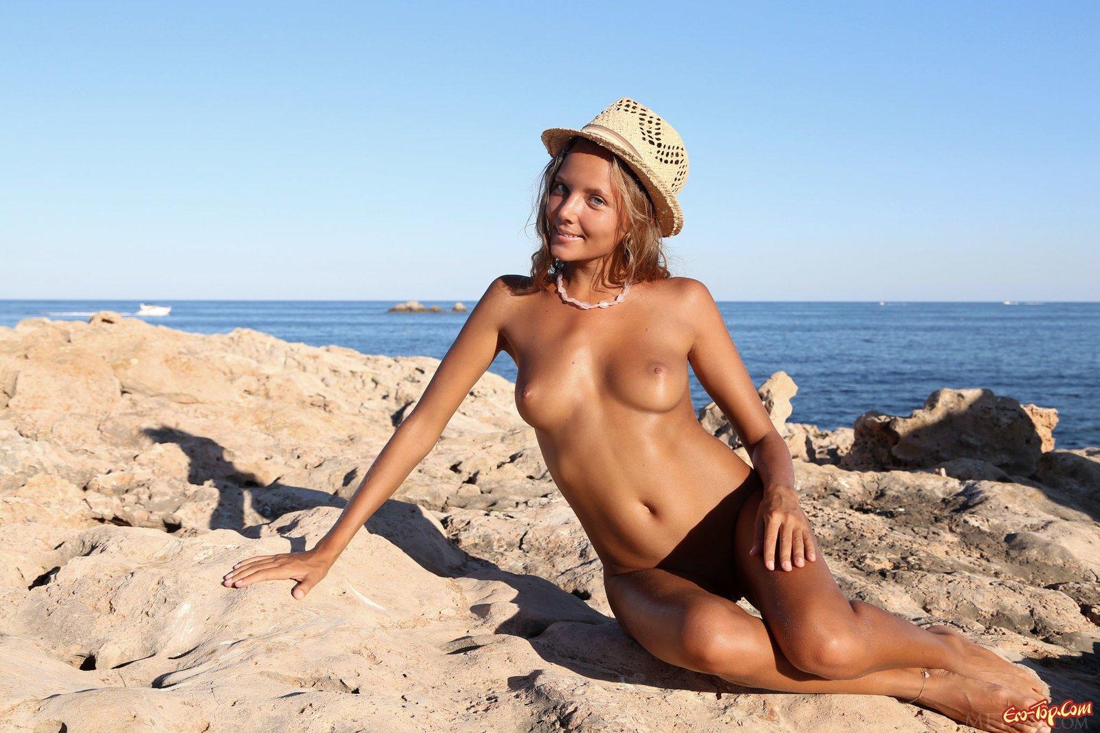Загорелая деваха делает селфи недалеко от моря