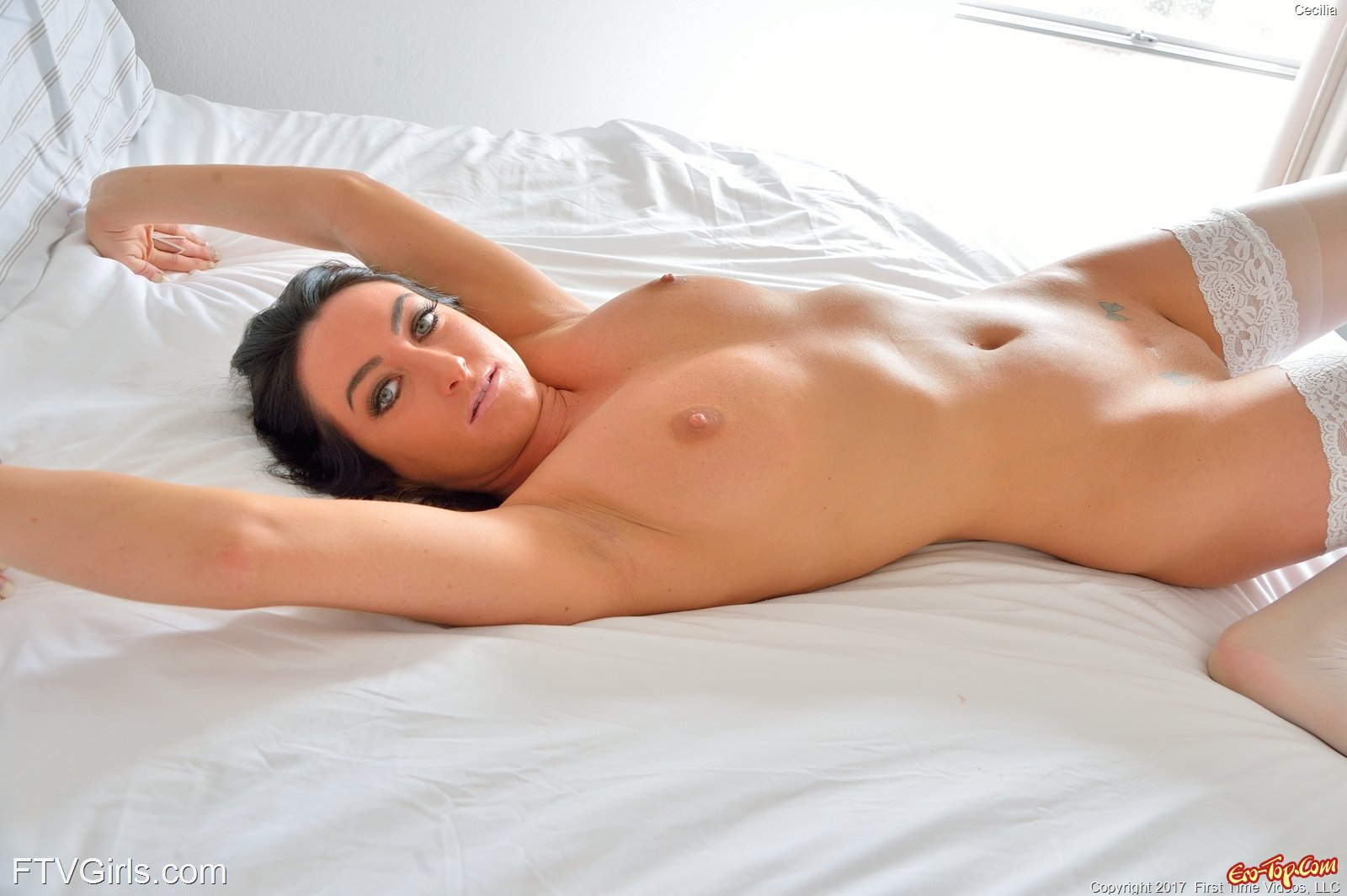 Брюнетка светит попку и гладкую киску в постели