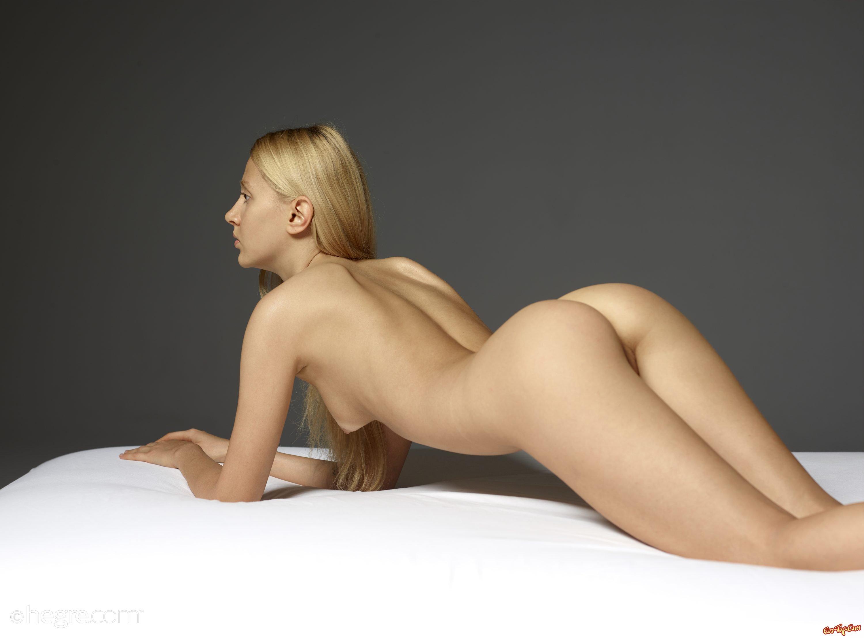 Светлая порно звезда выставляет напоказ вагину на белых простынях