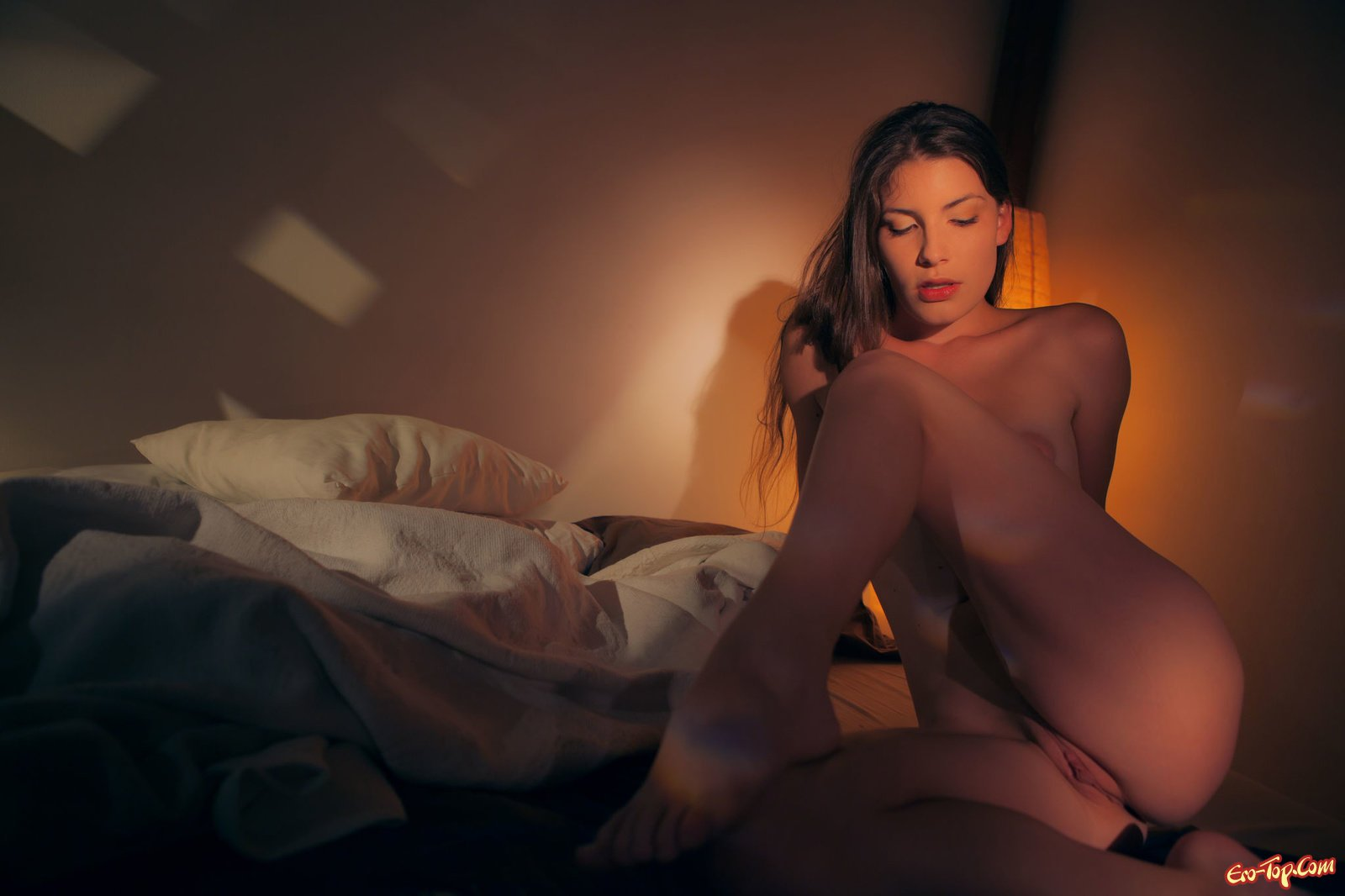 Обнаженная сучка блистает грудь сидя в кровати