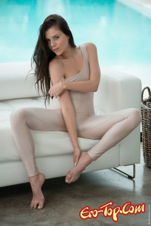 Брюнетка эротично разделась на белом диване
