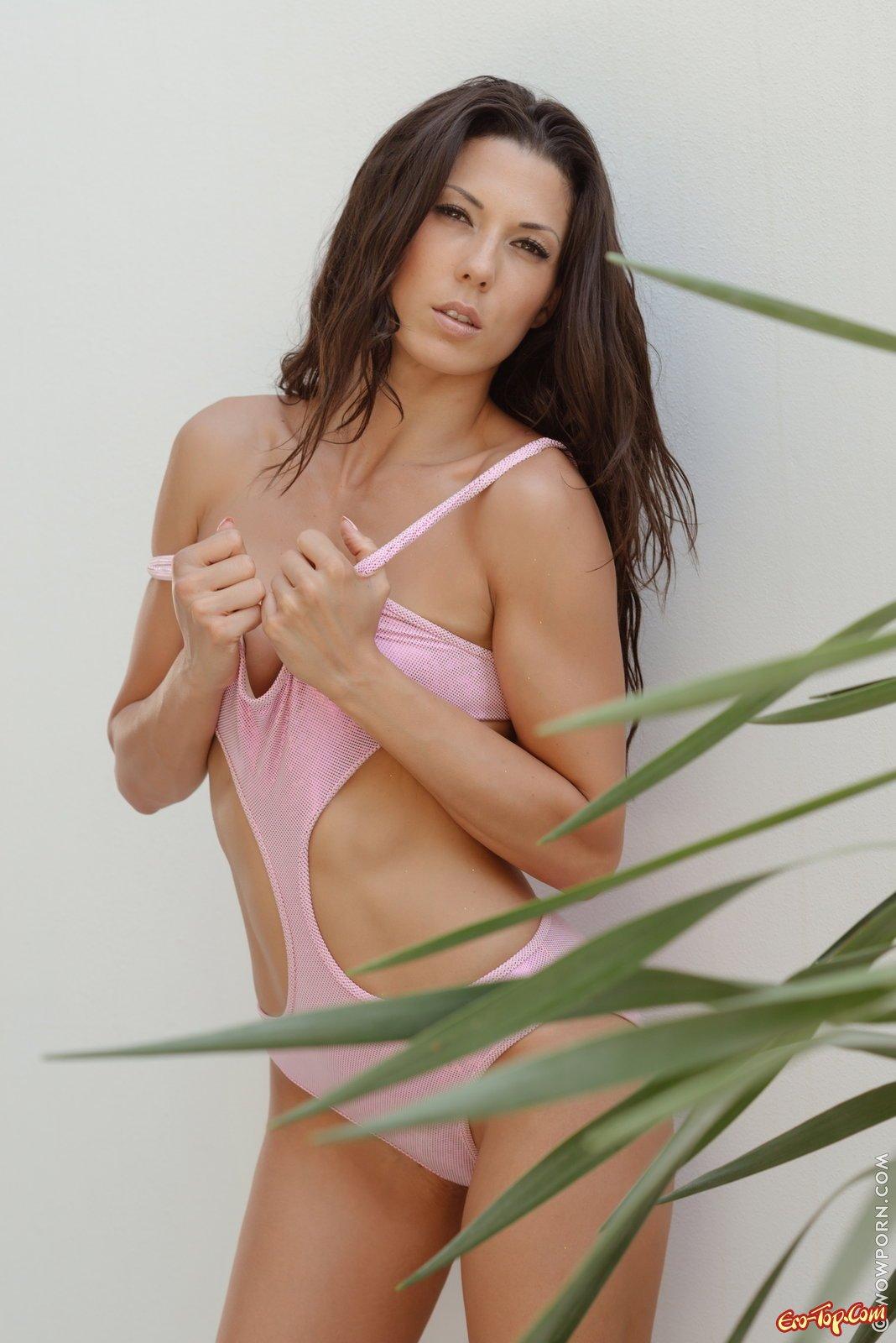 Сексуальная девушка снимает розовый купальник