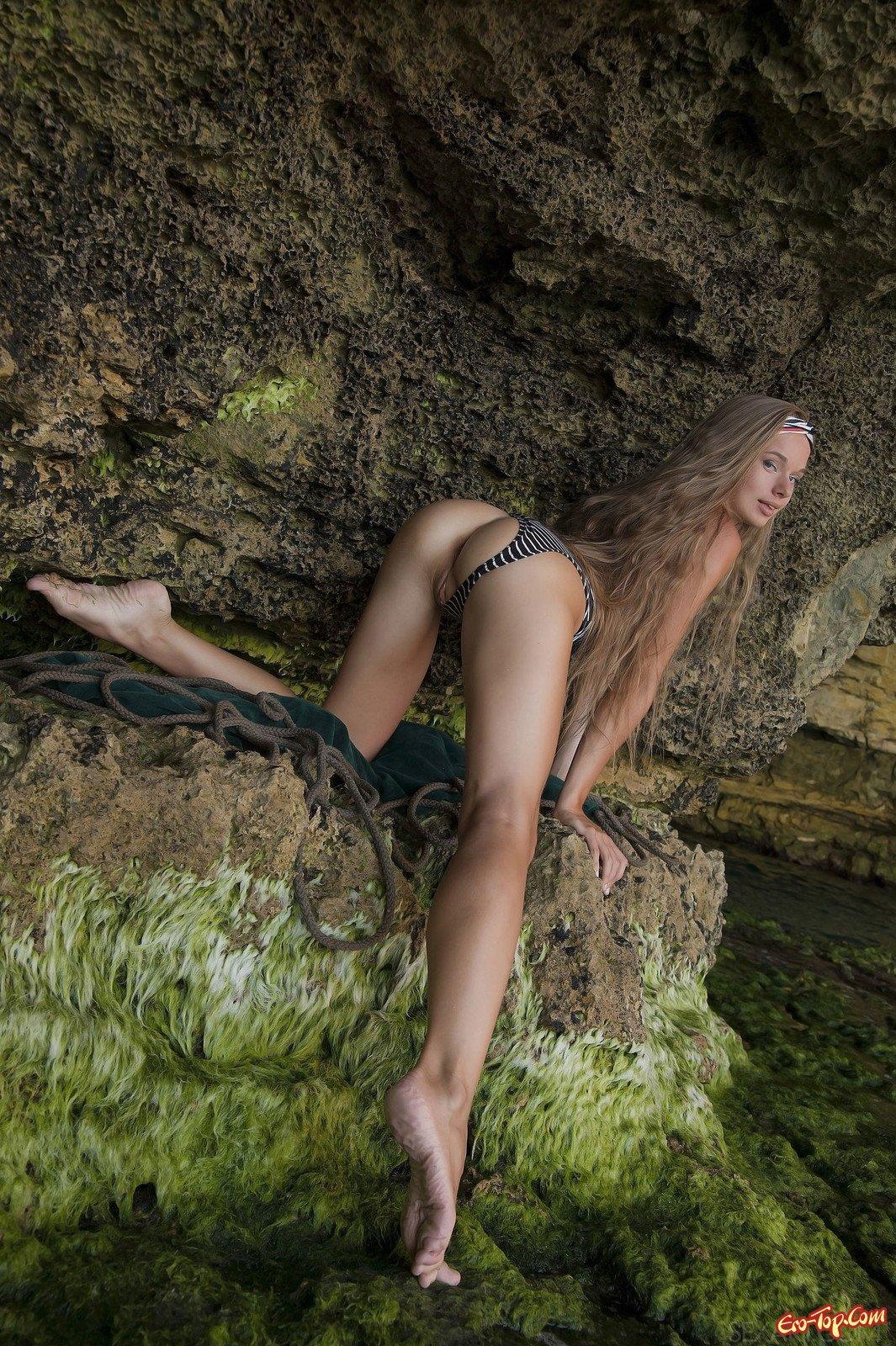 Молодуха в купальнике позирует в пещере