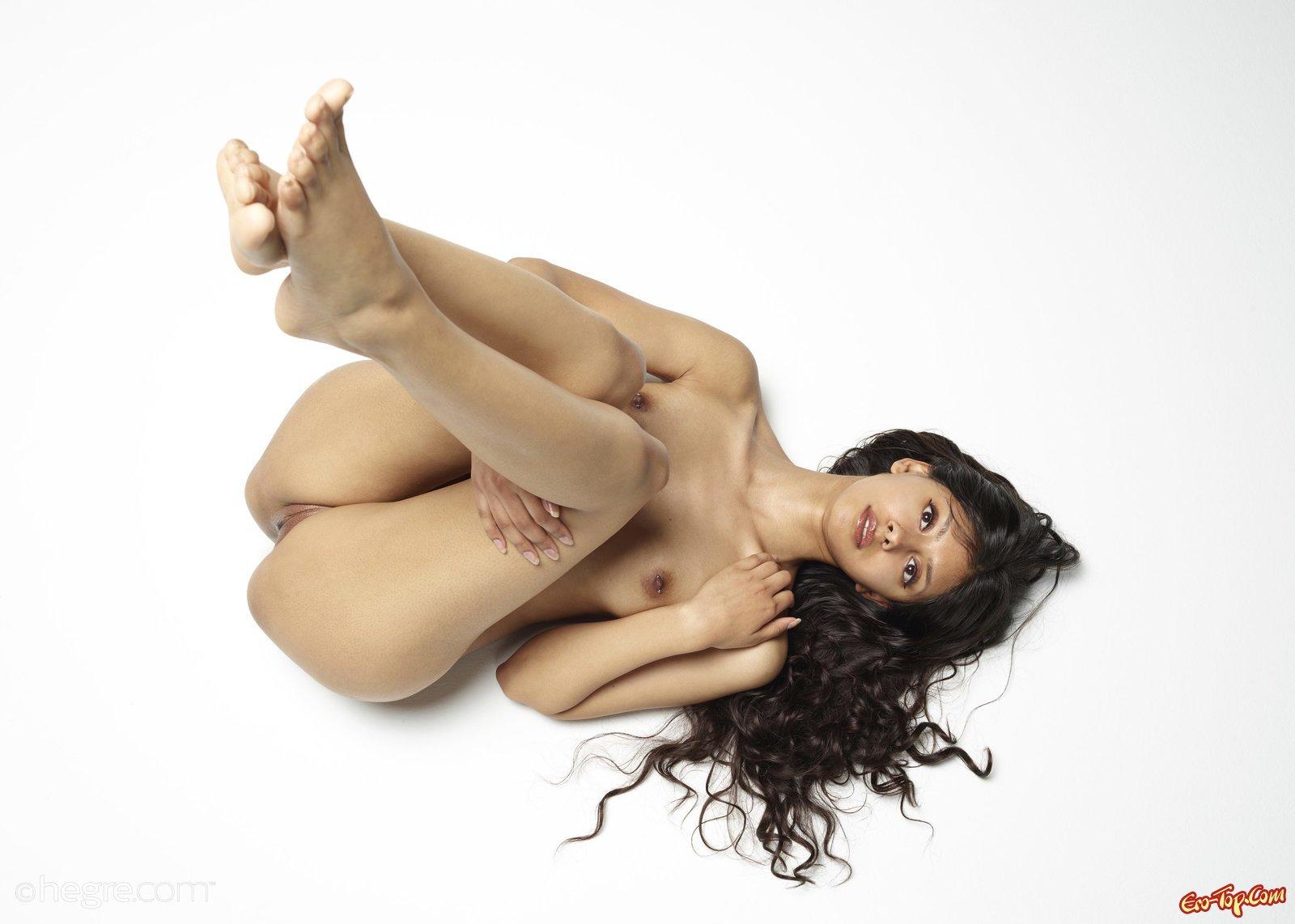 Обнаженная темноволосая девка с пирсингом в сосках снимается на полу