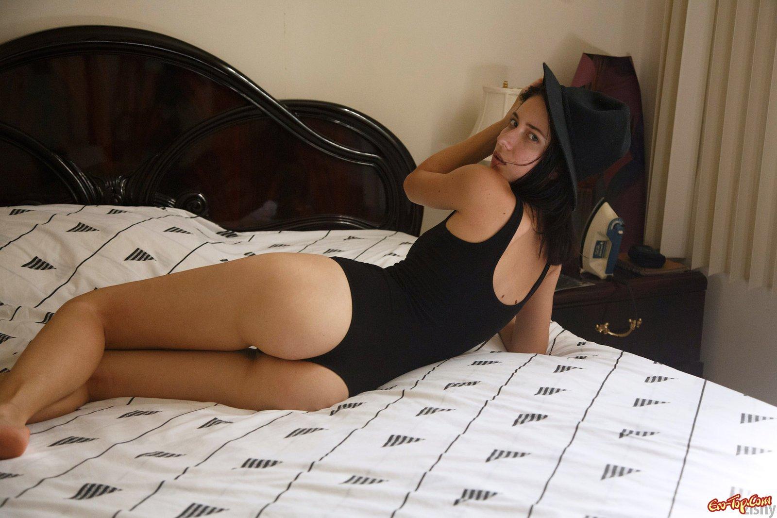 Брюнетка в черном купальнике позирует в спальне