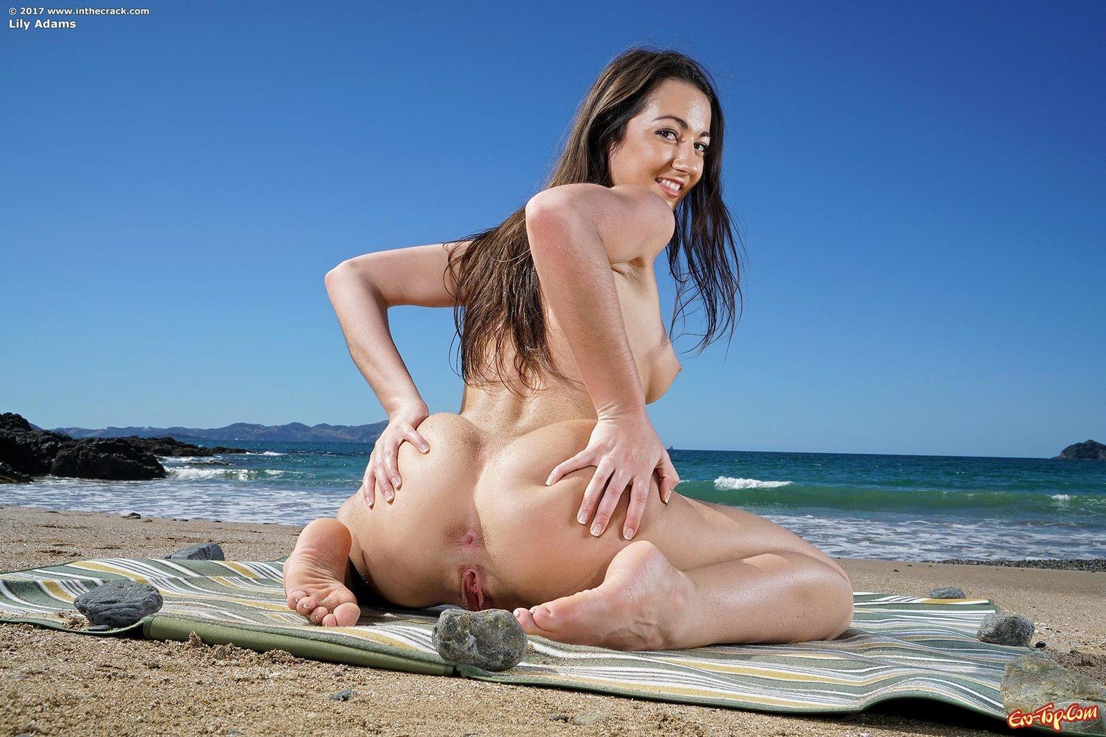 Сексуальная брюнетка раздвигает ноги на пляже у моря