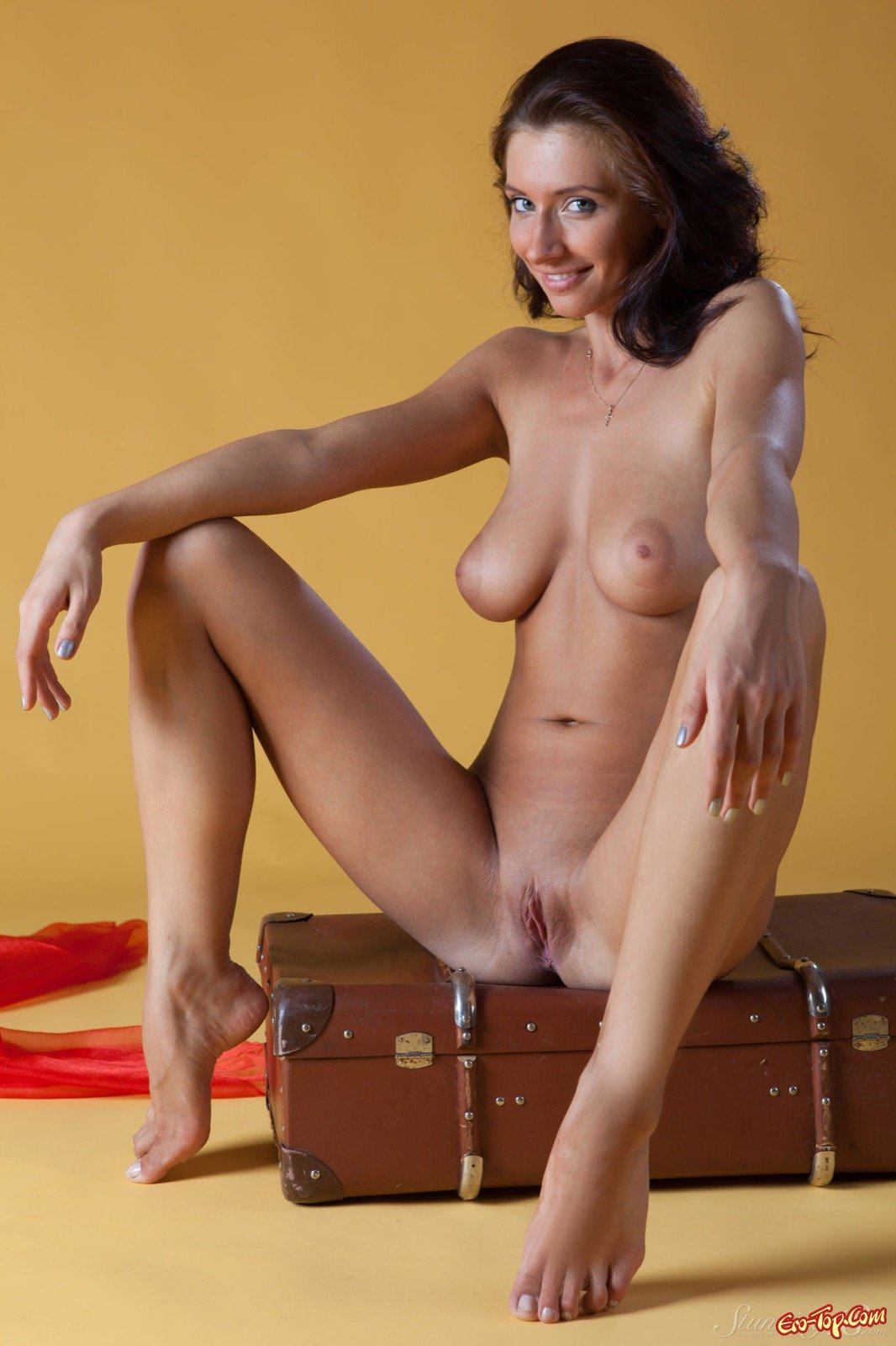 Раздетая загоревшая красавица снимается рядом с чемоданом