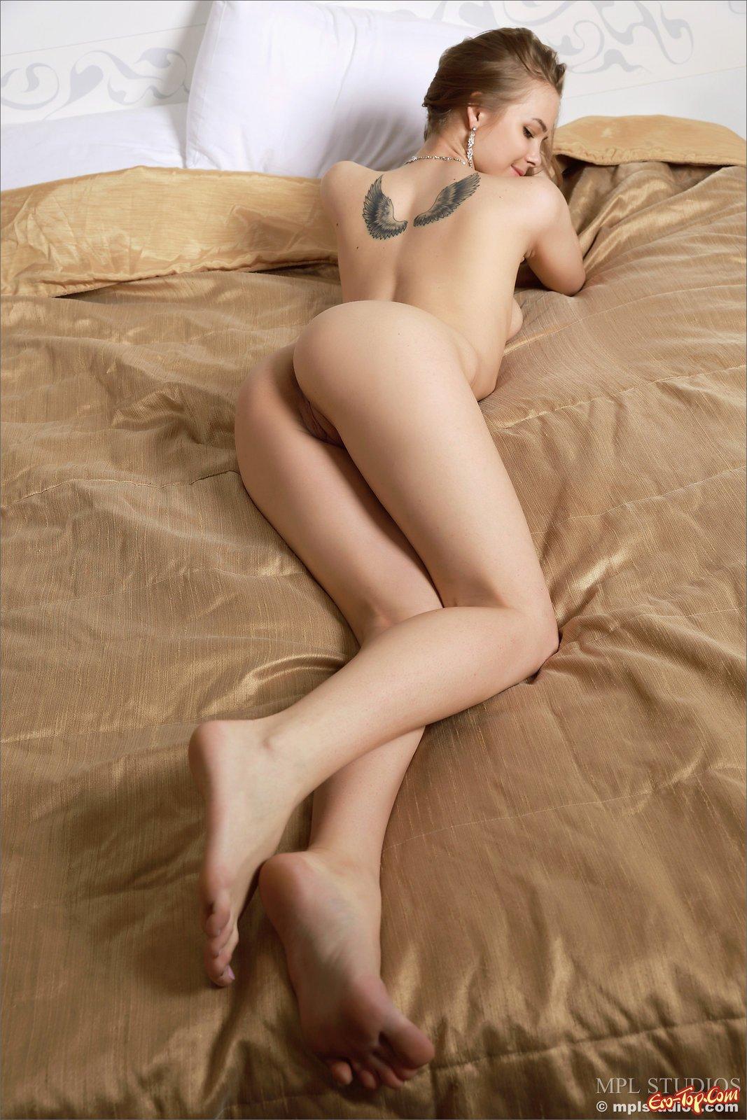 Голая блонди с роскошной попой лежит в постели
