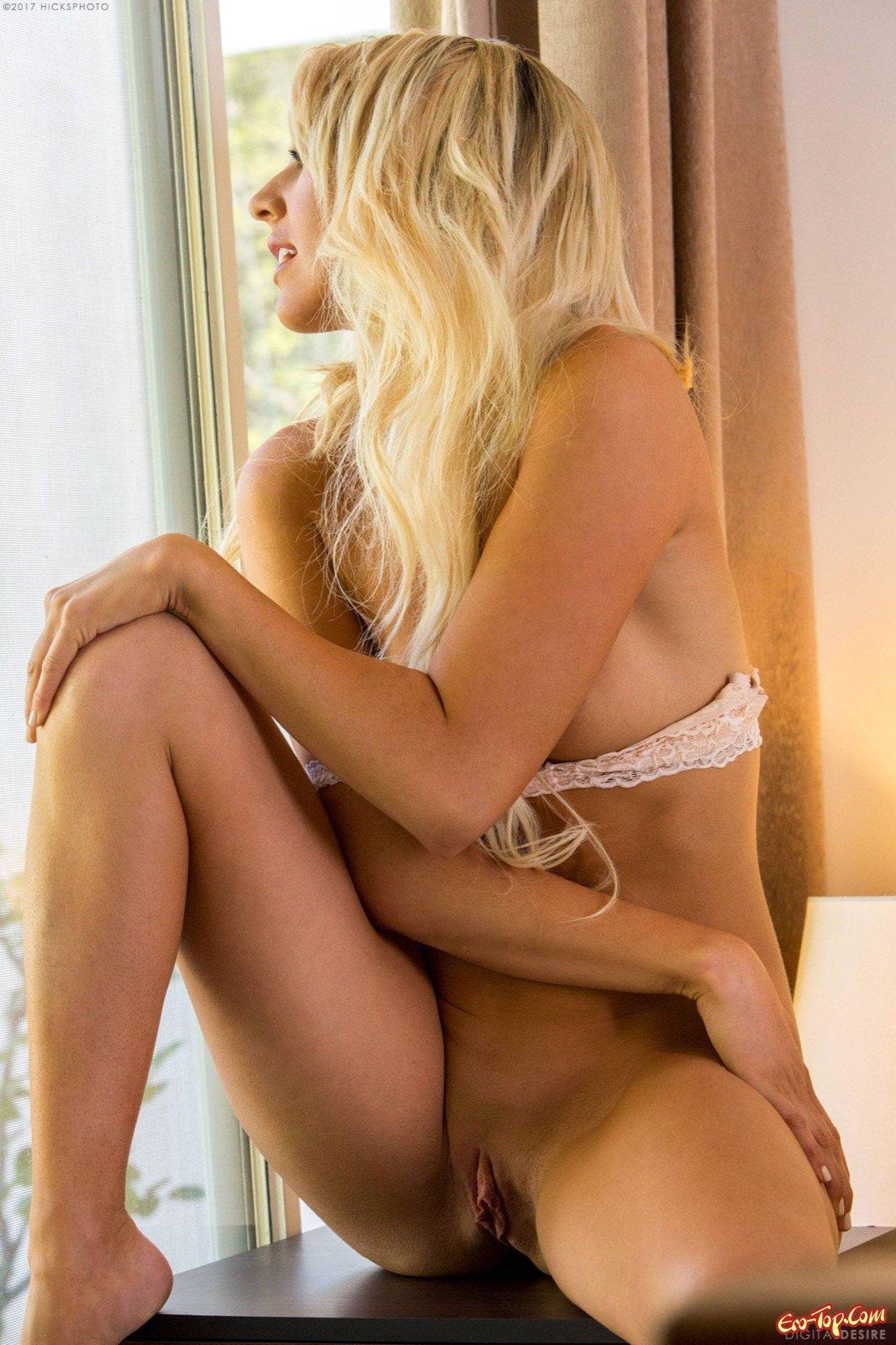 Жаркая блондинка светит сексуальным телом в постели