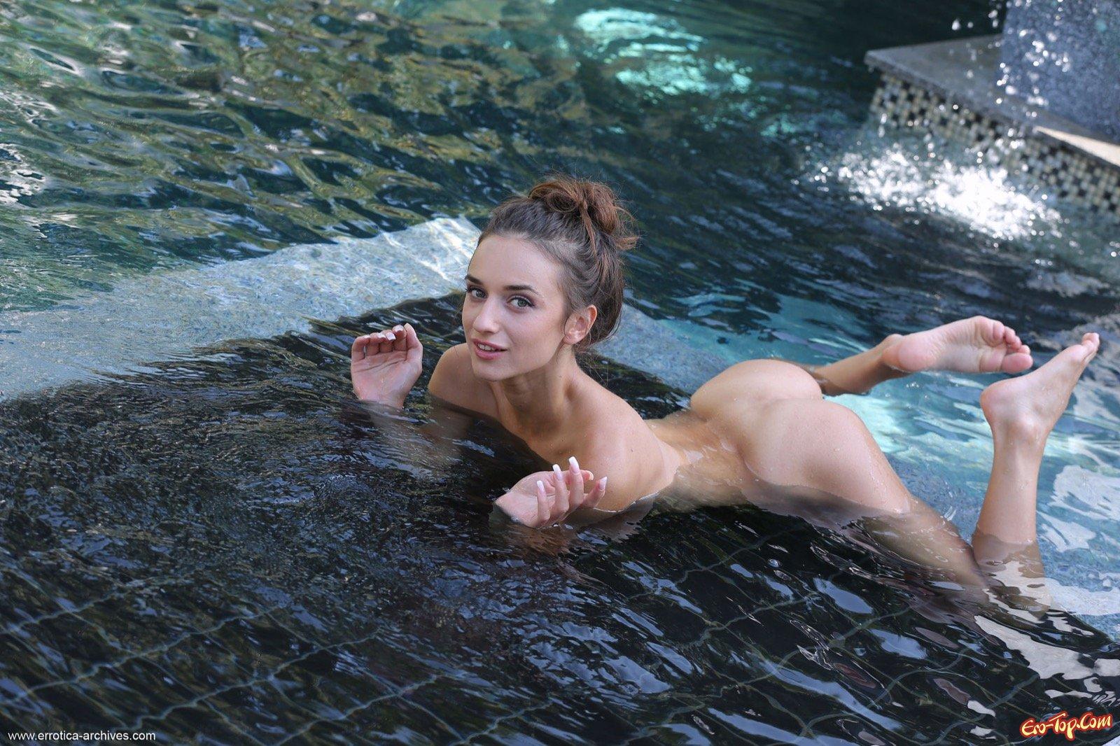 Голая девушка с плоским животиком в бассейне