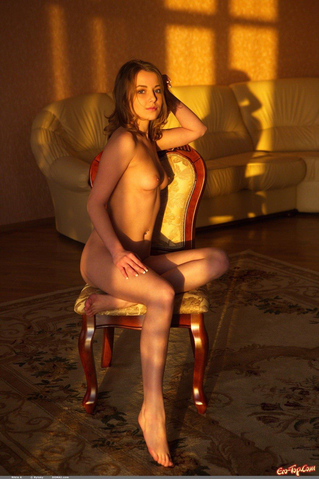 Брюнеточка с пирсингом в пупке фотографируется раздетой на стуле