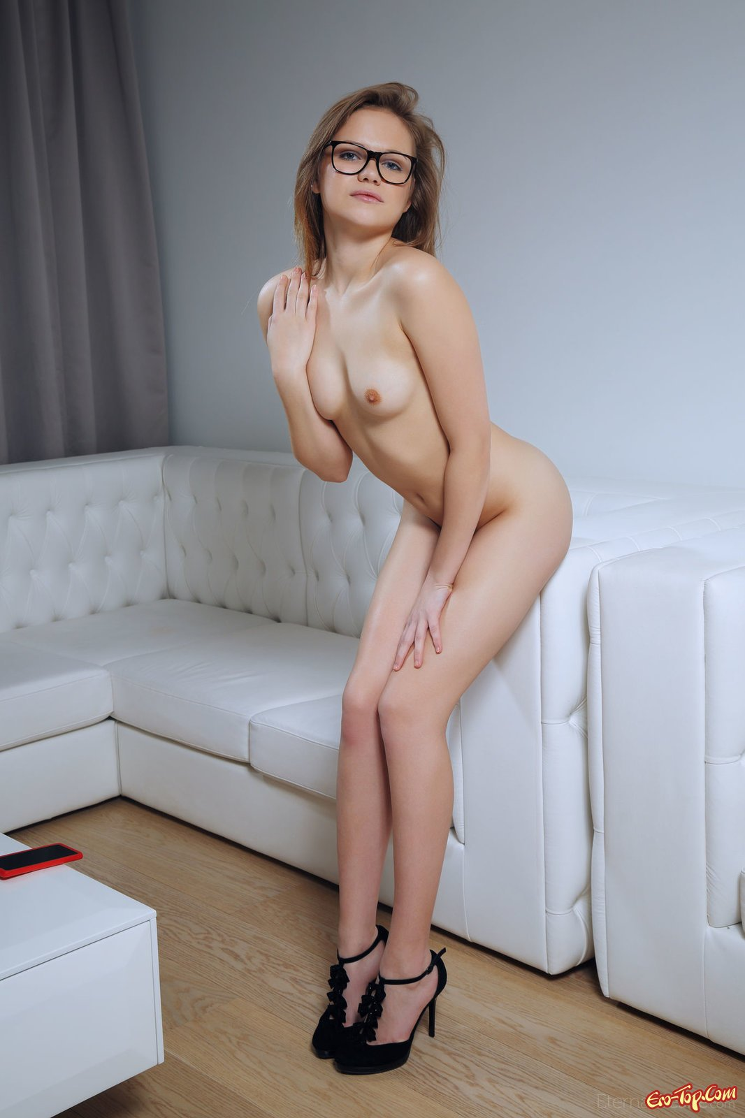 Молодая девушка в очках позирует голой на диване