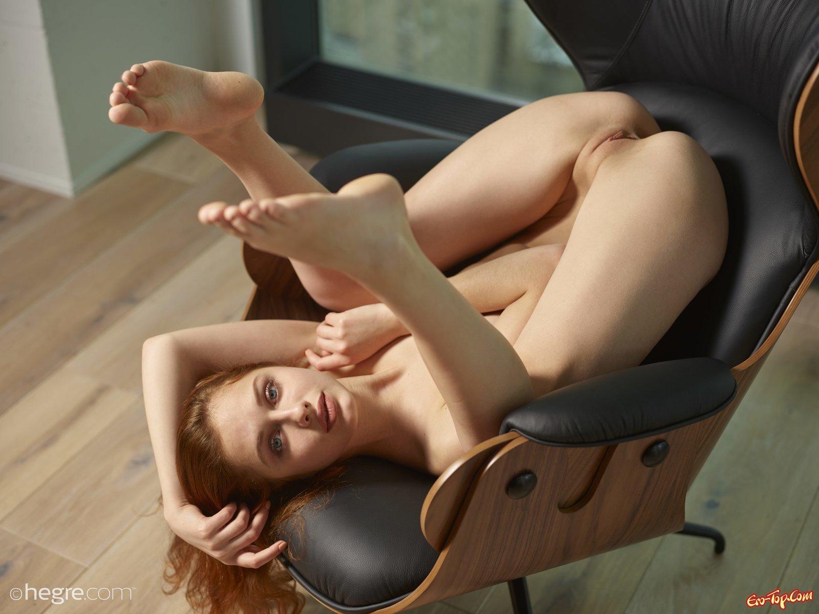 Раздетая рыженькая тёлка фотографируется в кожаном кресле