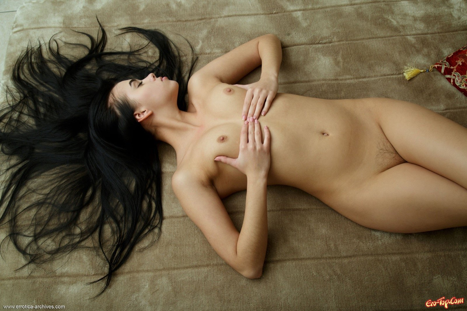 Сексуальная брюнетка позирует в обнаженном виде