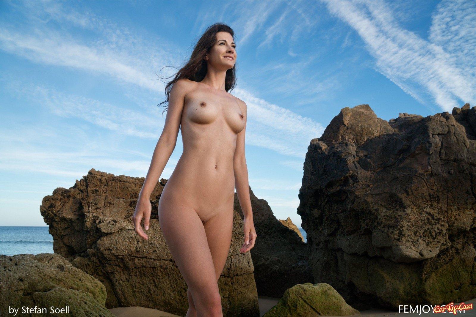 Голая девушка показывает стройное тело на природе