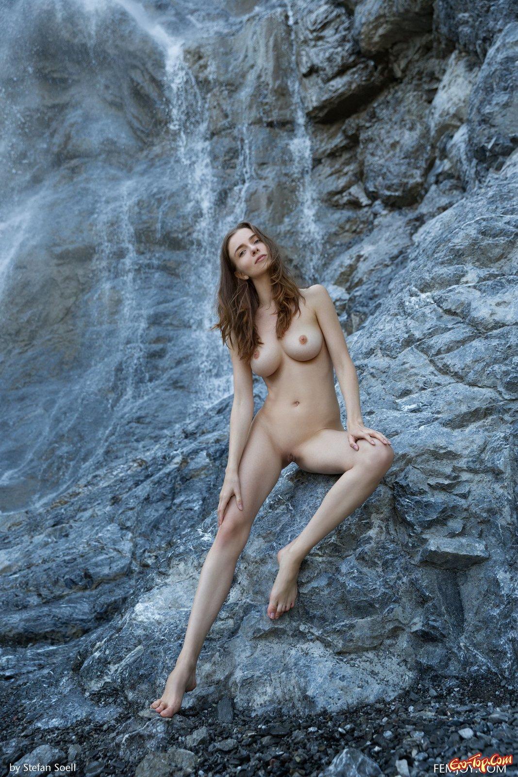 Обнаженная шатенка показала грудь стоя у водопада
